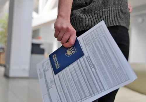 Девушка держит анкету на визу и украинский паспорт