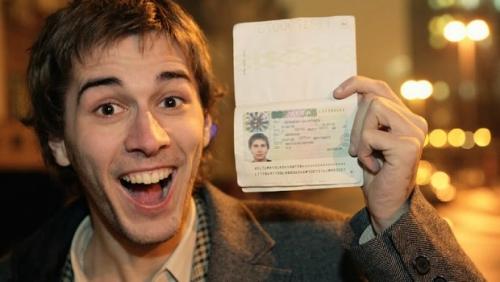 Счастливый молодой человек с шенгенской визой